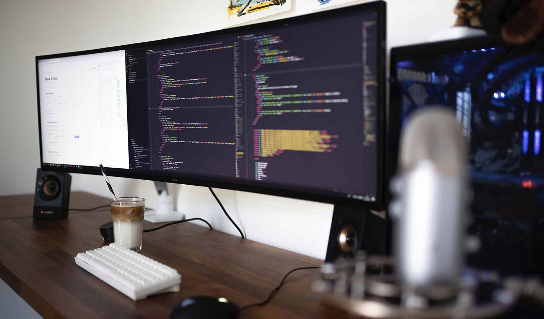 Software developers monitors and computer using Sinatra, Haml, & Postgres